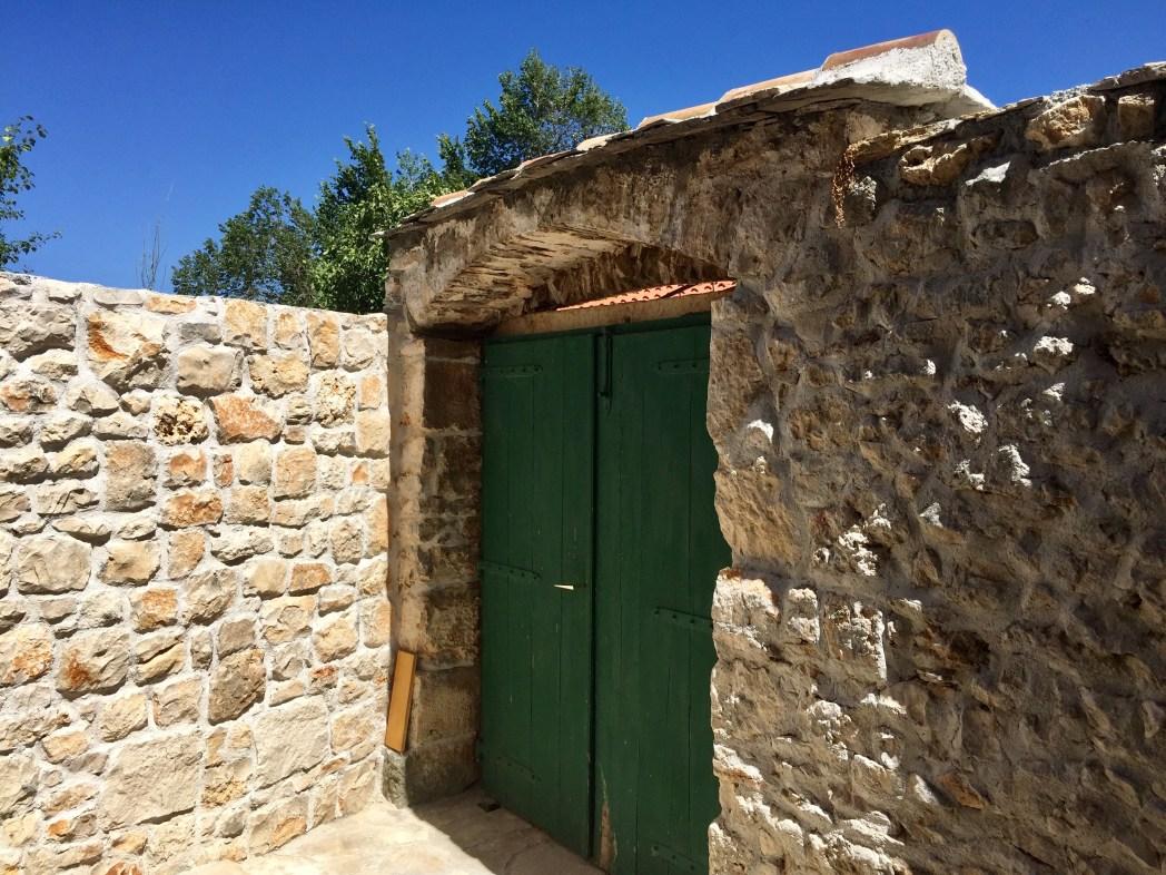 岩の壁とグリーンのドア、真っ青な空とのコントラストが素敵すぎたエントランス