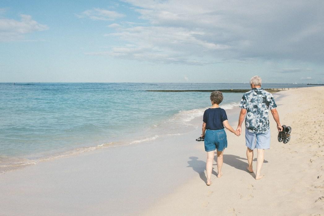 朝のワイキキ・ビーチを散歩する老夫婦