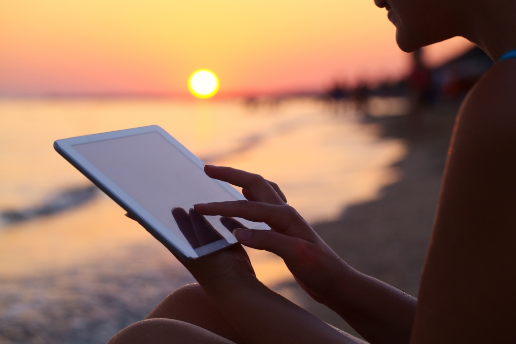 woman using ipad on beach