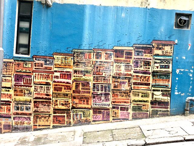 壁一面が真っ青に塗られ、その上に香港の旧家が描かれたストリートアート