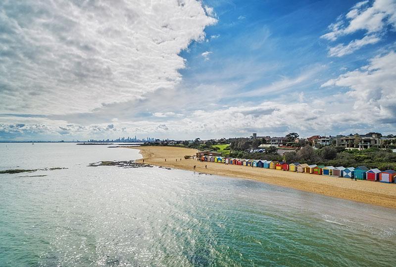 メルボルンの市街地を背景に、色とりどりのビーチ小屋が立ち並ぶ絶景スポット