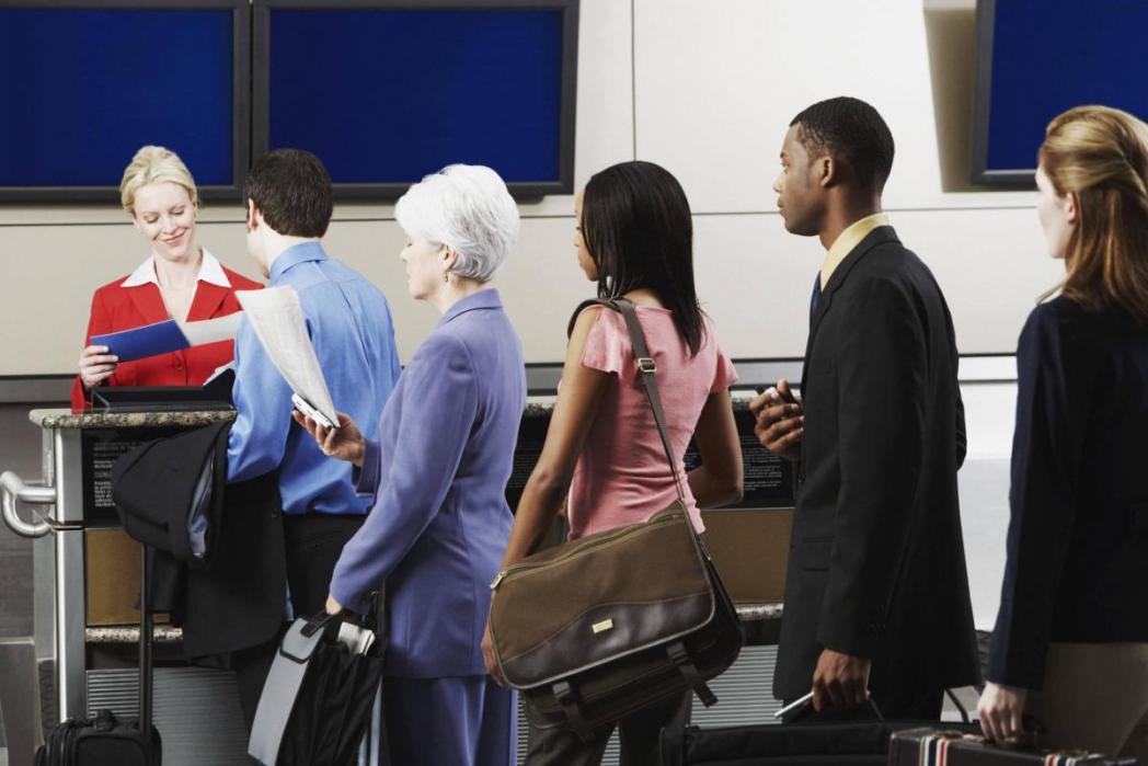 チェックインカウンターに並ぶ乗客、空港