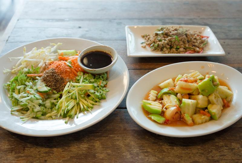 ライスサラダの「カオヤム」(写真左)と、ドライカレー「クワクリン」(写真右上)、りんごのスパイシーサラダ「タムアップル」(写真右下)